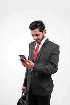 Jonge indiase zakenman laptoptas in de hand houden en mobiel gebruiken