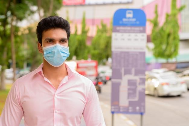 Jonge indiase zakenman masker dragen tijdens het wachten bij de bushalte