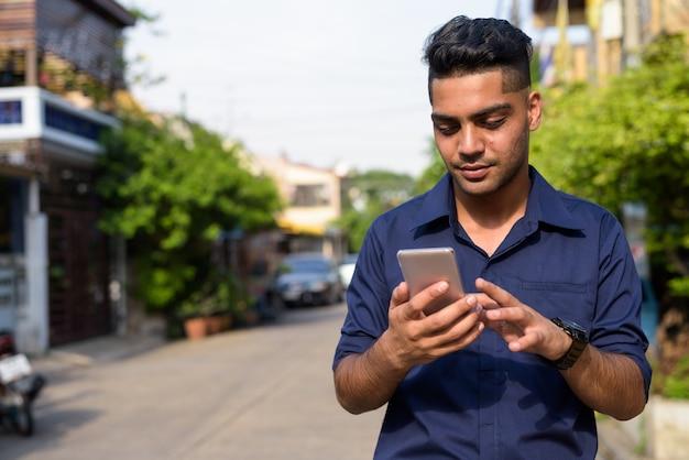 Jonge indiase zakenman met behulp van mobiele telefoon in de straten buitenshuis