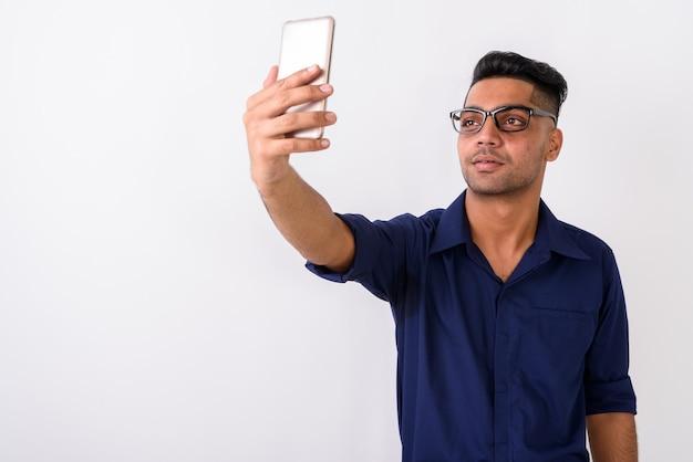 Jonge indiase zakenman met behulp van mobiele telefoon op wit