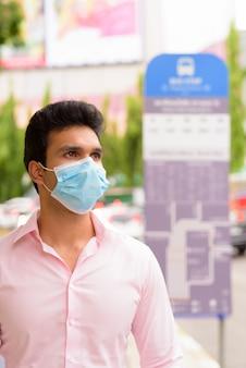 Jonge indiase zakenman met masker denken en wachten bij de bushalte