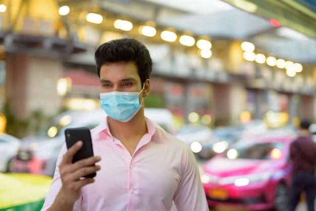 Jonge indiase zakenman met masker met behulp van telefoon in de straten van de stad