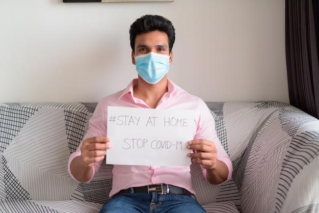 Jonge indiase zakenman met masker met stay at home teken zittend in de woonkamer onder quarantaine