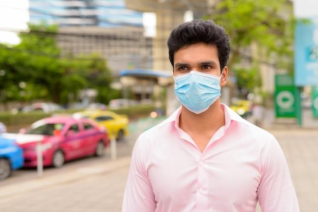 Jonge indiase zakenman met masker te wachten bij taxistation in de stad