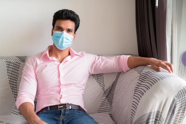 Jonge indiase zakenman met masker thuis blijven in quarantaine