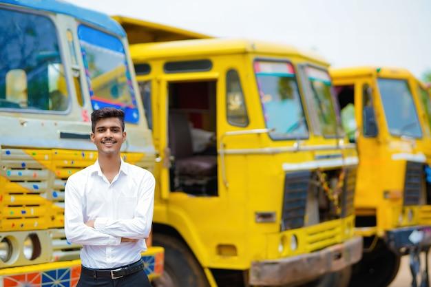 Jonge indiase zakenman met zijn vrachtauto of vrachtwagen.