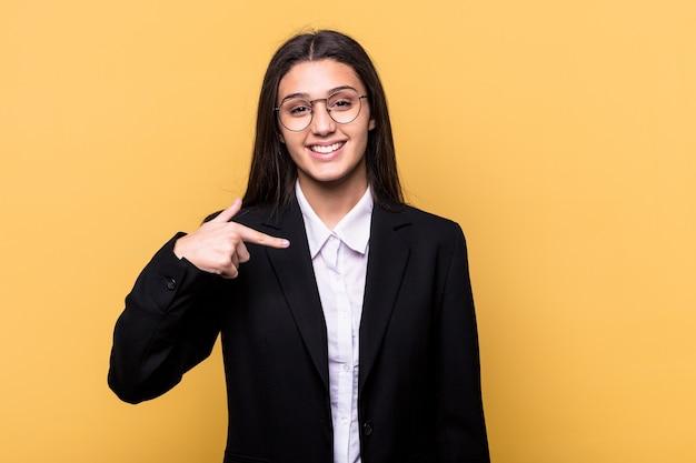 Jonge indiase zakenvrouw geïsoleerd op gele muur persoon met de hand wijzend naar een shirt kopiëren ruimte, trots en zelfverzekerd