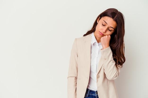Jonge indiase zakenvrouw geïsoleerd op wit die zich verdrietig en peinzend voelt, kijkend naar kopieerruimte.