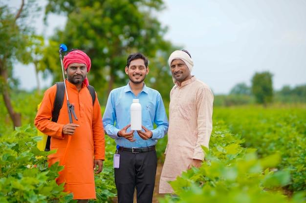 Jonge indische agronoom die fles met vloeibare mest aan boer geeft.