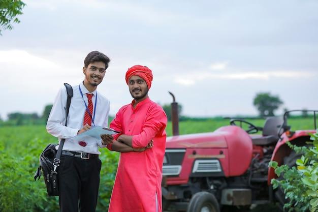 Jonge indische bankambtenaar die detail van leningsdocument toont aan landbouwer bij veld