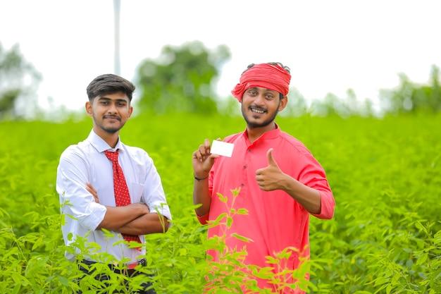 Jonge indische bankier en landbouwer die kaart tonen bij groen gebied