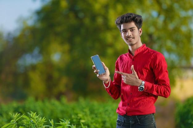 Jonge indische bankstafmedewerker bij veld met laptop