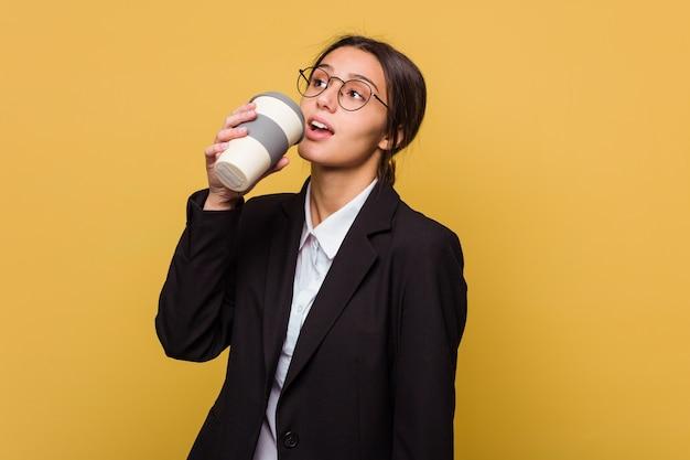 Jonge indische bedrijfsvrouw die een afhaalmaaltijden geïsoleerde koffie drinken