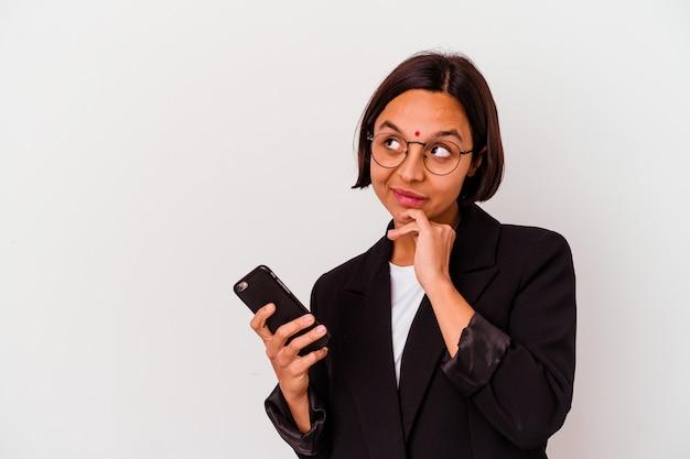 Jonge indische bedrijfsvrouw die een geïsoleerde telefoon houdt die zijdelings met twijfelachtige en sceptische uitdrukking kijkt.