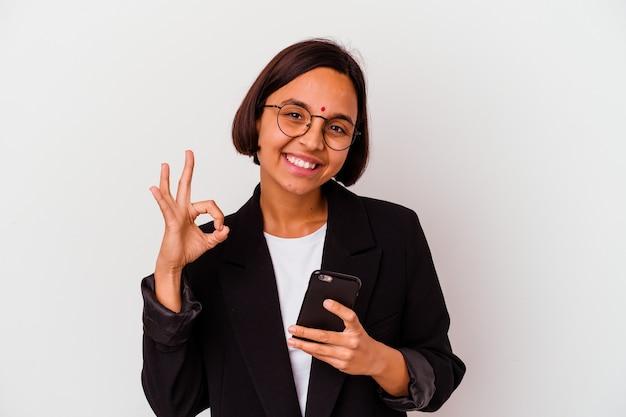 Jonge indische bedrijfsvrouw die een telefoon geïsoleerd vrolijk en zeker houdt die ok gebaar toont.