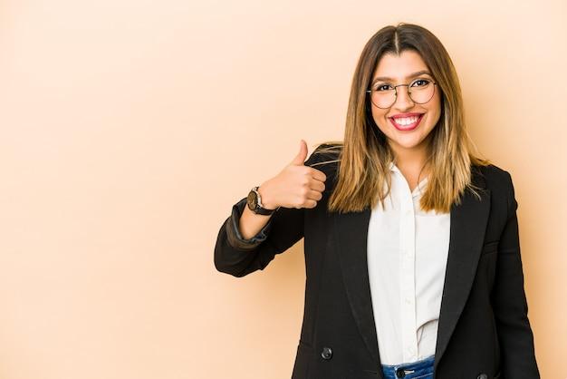 Jonge indische bedrijfsvrouw die en duim glimlacht opheft geïsoleerd