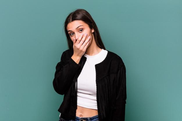 Jonge indische die vrouw op blauwe muur wordt geïsoleerd die mond behandelt met handen die bezorgd kijken
