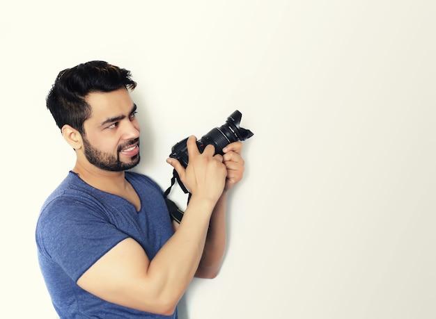 Jonge indische fotograaf die een dslr-fotocamera houdt die op witte achtergrond wordt geïsoleerd