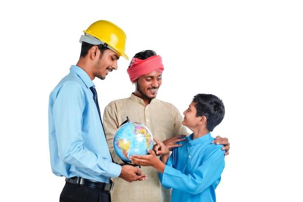 Jonge indische ingenieur die wat detail toont aan boer en zijn kind in wereldbolkaart.