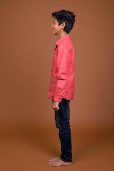 Jonge indische jongen die slimme vrijetijdskleding draagt tegen bruine achtergrond