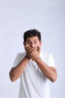 Jonge indische man geschokt en mond bedekken met hand.