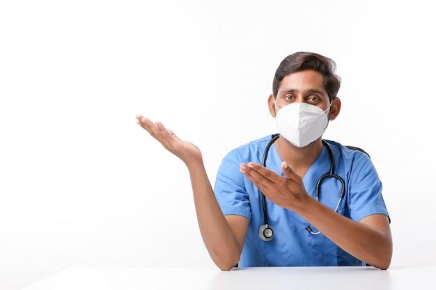 Jonge indische mannelijke arts die een masker draagt en met de hand naar de kliniek wijst.