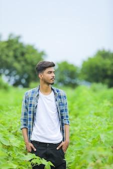 Jonge indische mens die uitdrukking over aardachtergrond toont