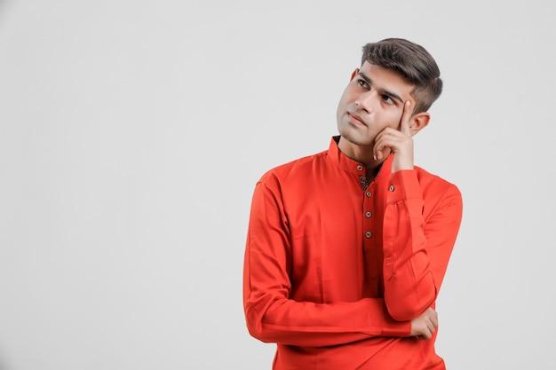 Jonge indische mens in rood overhemd en het denken groot idee op wit