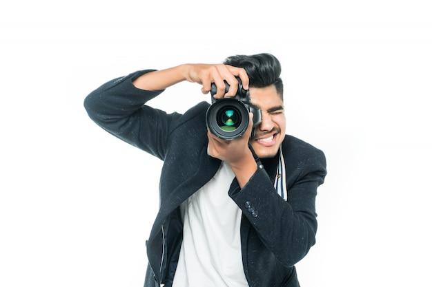 Jonge indische mens met camera die over witte achtergrond wordt geïsoleerd
