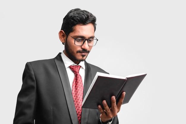 Jonge indische succesvolle bedrijfsmens of stafmedewerker die bril draagt en boek leest
