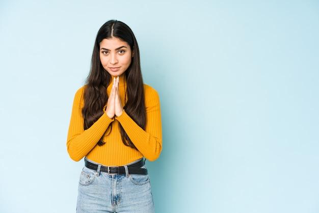 Jonge indische vrouw bij het blauwe muur bidden, die toewijding tonen