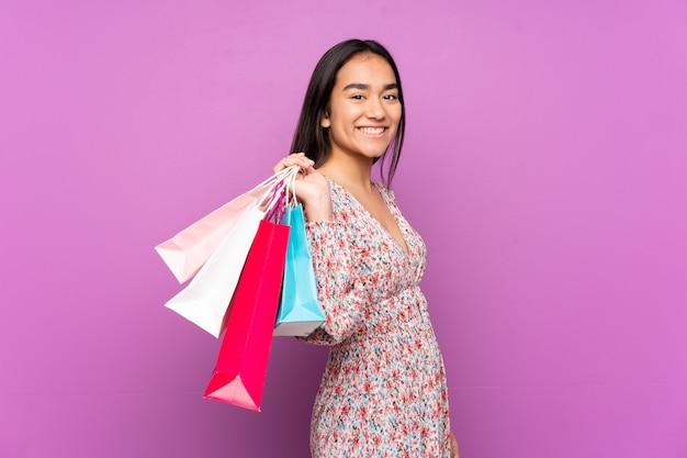 Jonge indische vrouw die bij purpere muurholding het winkelen zakken en het glimlachen wordt geïsoleerd