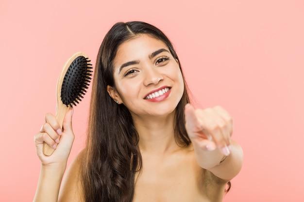 Jonge indische vrouw die een haarborstel vrolijke glimlachen houden richtend aan voorzijde.