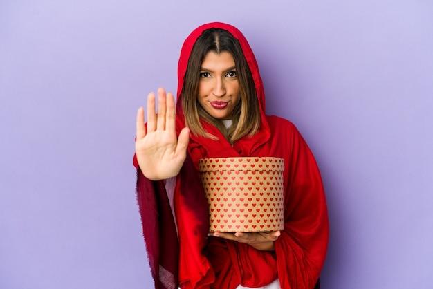 Jonge indische vrouw die een hijab draagt die een geïsoleerde gift van de valentijnskaartendag houdt status met uitgestrekte hand die stopbord toont, dat u verhindert.