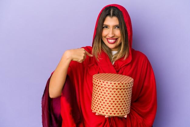 Jonge indische vrouw die een hijab draagt die een geïsoleerde valentijnskaartendaggift houdt die met de hand naar de ruimte van een overhemdskopie wijst, trots en zelfverzekerd