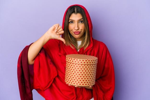 Jonge indische vrouw die een hijab draagt die een geïsoleerde valentijnskaartendaggift houdt met een afkeergebaar, duimen naar beneden. meningsverschil concept.