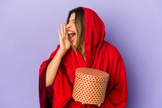 Jonge indische vrouw die een hijab draagt die een geïsoleerde valentijnskaartendaggift houdt schreeuwen en palm dichtbij geopende mond houdt.