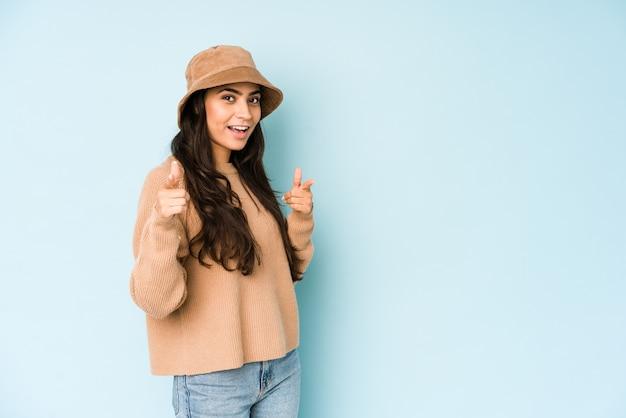 Jonge indische vrouw die een hoed draagt die op blauw wordt geïsoleerd dat aan voorzijde met vingers richt.