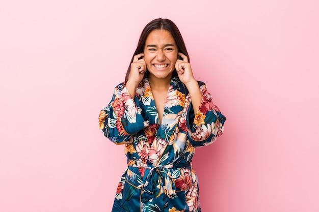 Jonge indische vrouw die een kimonopyjama draagt die oren behandelt met handen.