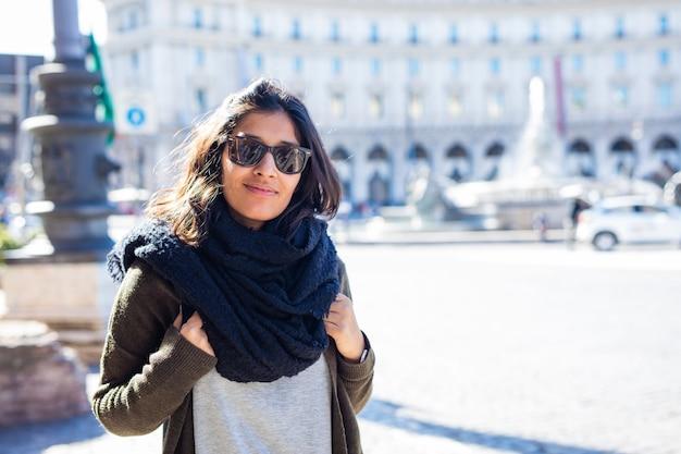 Jonge indische vrouw die in de stad glimlacht