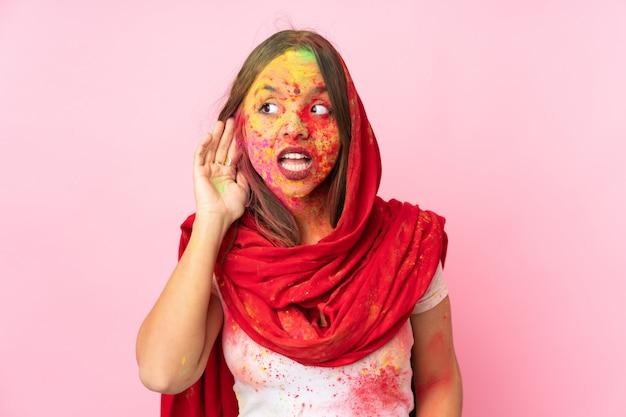 Jonge indische vrouw die met kleurrijk holipoeder op haar gezicht op roze muur aan iets luistert door hand op het oor te zetten
