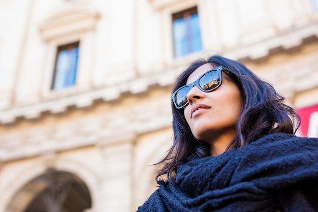 Jonge indische vrouw die omhoog in de stad kijkt