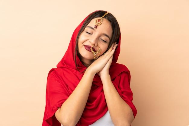 Jonge indische vrouw die op beige muur wordt geïsoleerd die slaapgebaar in dorable uitdrukking maakt