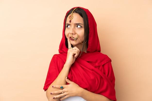 Jonge indische vrouw die op beige muur wordt geïsoleerd die twijfels en het denken heeft