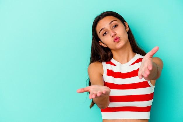 Jonge indische vrouw die op blauwe muur wordt geïsoleerd die lippen vouwt en palmen houdt om luchtkus te verzenden.