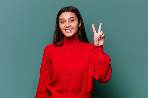 Jonge indische vrouw die op blauwe muur wordt geïsoleerd die overwinningsteken toont en breed glimlacht