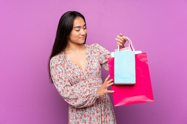 Jonge indische vrouw die op purpere het winkelen van de muurholding zakken wordt geïsoleerd