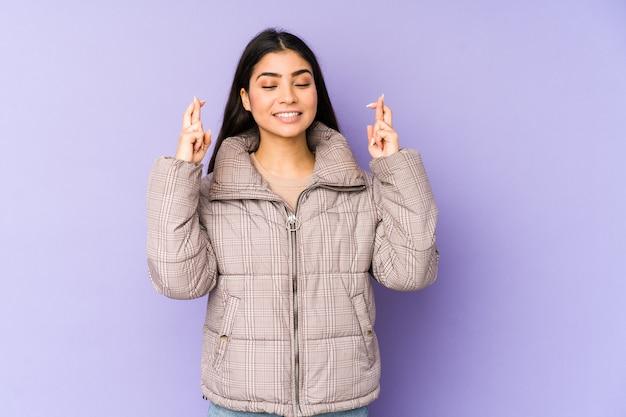 Jonge indische vrouw die op purpere kruisende vingers wordt geïsoleerd voor het hebben van geluk