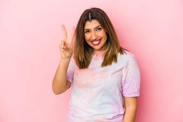 Jonge indische vrouw die op roze muur wordt geïsoleerd, die nummer twee met vingers toont.