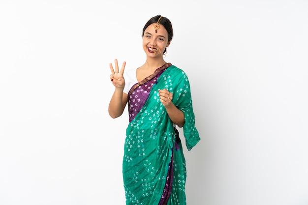 Jonge indische vrouw die op wit wordt geïsoleerd gelukkig en tellend drie met vingers